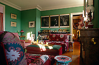 A photographic triptych by Bill Henson hangs above a bookcase on the far wall of this green painted living room with sofas upholstered in susani fabric