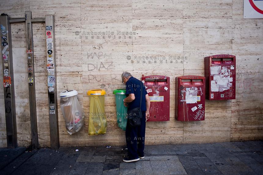 Un anziano signore rovista in fatiscenti contenitori della spazzatura all'ingresso della Stazione Termini.<br /> An older man scouring garbage at the main entrance of Termini station