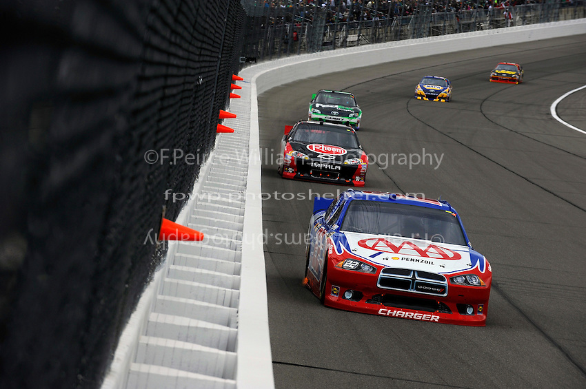 A. J. Allmendinger (#22) leads Kevin Harvick (#29) and Denny Hamlin, (#11) FedEx Ground Camry.