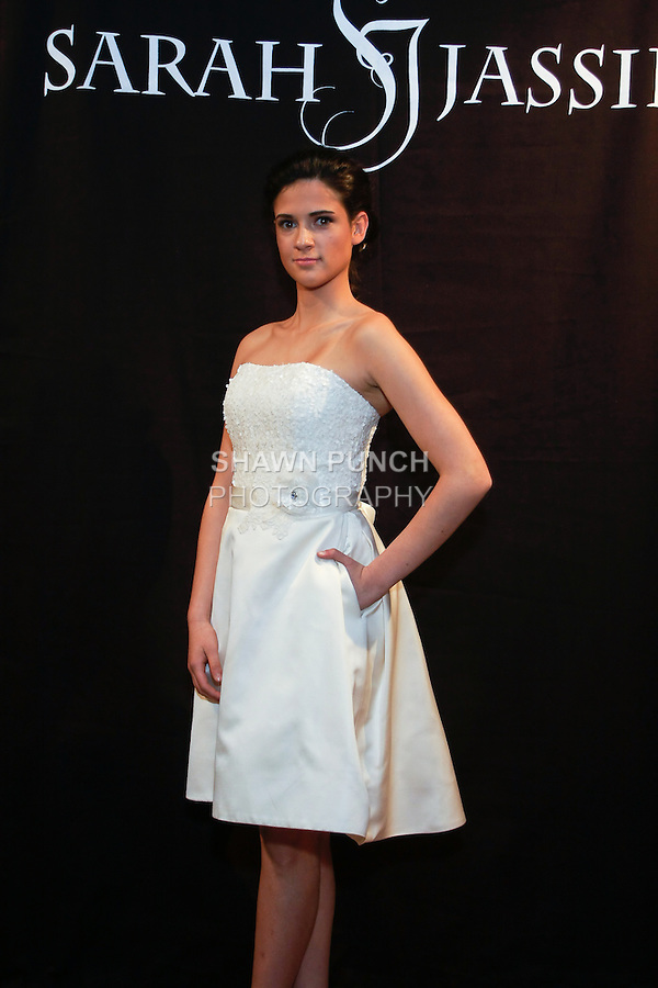 """Model poses in a Loulou Bridal dress - strapless short satin dress with sequin bodice, by Sarah Jassir, for the Sarah Jassir Spring 2013 """"La Reve: The Dream"""" collection, during Bridal Fashion Week New York."""