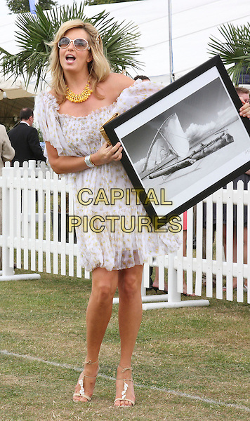 PENNY LANCASTER STEWART .Duke Of Essex Polo Trophy at Gaynes Park, Epping, Essex, England, UK,.July 4th 2009..full length white sheer puff sleeve off the shoulder dress blouson strappy sandals holding picture print mouth open funny .CAP/ROS.©Steve Ross/Capital Pictures