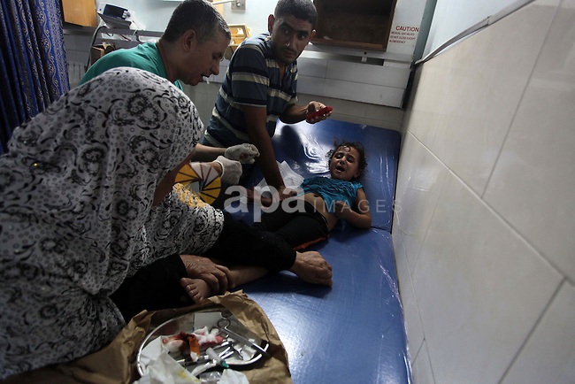 A Palestinian girl, who medics said was injured by Israeli shelling, receives treatment at al-Shifa hospital in Gaza City on July 21, 2014. World efforts to broker a ceasefire in war-torn Gaza gathered pace as Israel pressed a blistering 14-day assault on the enclave, pushing the Palestinian death toll to 561. Photo by Ashraf Amra