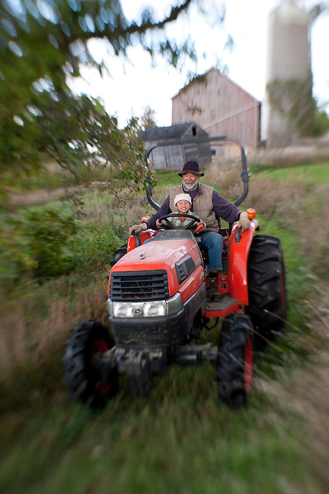 Holden Miller, 4, controls the steering wheel while going on a tractor ride with his grandfather, Dave Stute, at the Rasch/Stute farm in Argyle, Wis., during early autumn on Sept. 24, 2011. The two were seat-buckled into Stute's orange Kubota tractor.