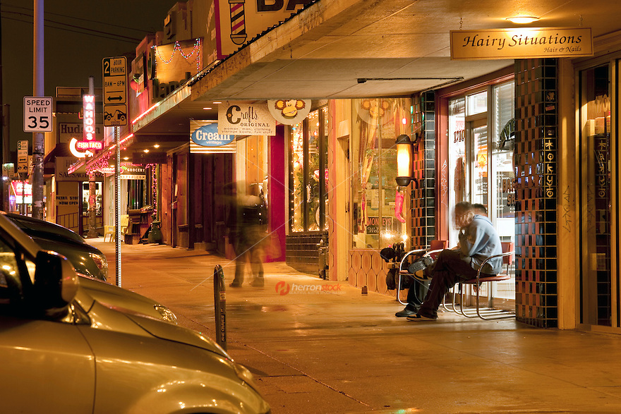 Nighttime view of South Congress Avenue's sidewalk showcases many eclectic retail shops - Stock Image.