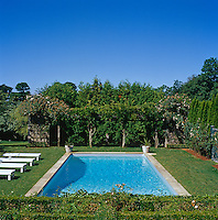 This manicured garden is dominated by a large azure-blue swimming pool