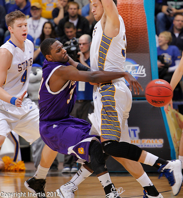 SIOUX FALLS, SD - MARCH 9:  Garret Covington #31 of Western Illinois passes around Cody Larson #34 of South Dakota State during their first round game at the 2014 Summit League Basketball Championships Sunday at the Sioux Falls Arena. At left is Jake Bittle #4 of South Dakota State. (Photo by Dick Carlson/Inertia)