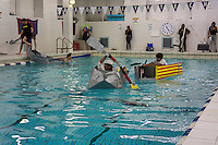 """Alex Penaranda, a senior, center, pilots his team's boat in the Brooklyn Technical High School Cardboard Boat Regatta in the school's pool in Brooklyn in New York on Friday, March 1, 2013. As part of Engineering Week the teams of students constructed boats made only of cardboard and duct tape. The team's assigned """"captain"""" piloted their boat from one end of the pool to the other and back in a heat with other boats, hopefully without sinking. The surviving boats were timed and the winners received bragging rights with an award also going to the most spectacular sinking. (© Richard B. Levine)"""
