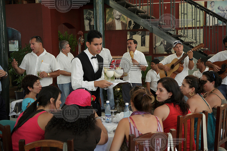 "Foreign tourists being served cocktails in a restaurant in Old Havana. Tourism is Cuba's mains source of hard currency earnings. It has also led to the ""dual economy"" where those working in tourism such as this waiter and the musicians in the background can earn much more money than workers in state jobs."