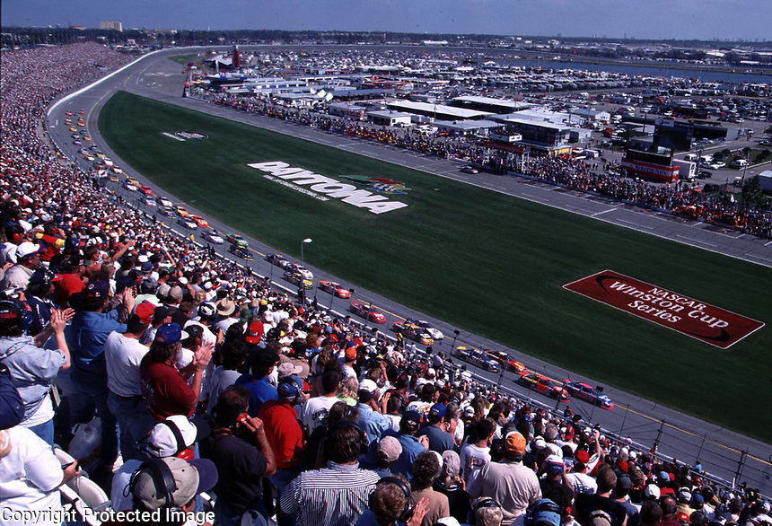 A huge crowd stands as the green flag waves to starts the 2000 Daytona 500 at Daytona International Speedway 2/20/00.(Photo by Brian Cleary)