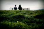 Two people sitting on a country bench with grass in the foreground