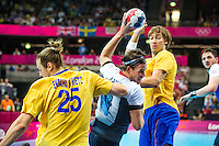 31 JUL 2012 - LONDON, GBR - Steven  Larsson (GBR) of Great Britain (centre, in white, blue and red) dives past Kim Ekdahl Du Rietz (SWE) of Sweden (left) as he shoots during the men's London 2012 Olympic Games Preliminary round match at The Copper Box in the Olympic Park, in Stratford, London, Great Britain .(PHOTO (C) 2012 NIGEL FARROW)