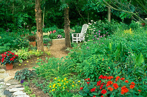 Shaded garden path with blooming flowers and white Adirondack chair, Missouri