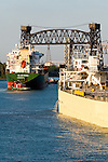 Two tugboats guide a large international grain vessel through the narrow channel between Lake Calumet and Lake Michigan on the south side of Chicago.