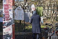 """Corona-Krise, Hilfe fuer Obdachlose.<br /> Menschen in Berlin haben fuer Obdachlose """"Spenden- und Gabenzaeune"""" eingerichtet. Dort haengen sie Bekleidung und haltbare Lebensmittel auf, die sich Obdachlose mitnehmen koennen.<br /> Im Bild: Ein Obdachloser nimmt Lebensmittel vom Spendenzaun an der Evangelische Kirchengemeinde am Weinberg in Berlin-Mitte.<br /> 24.3.2020, Berlin<br /> Copyright: Christian-Ditsch.de<br /> [NUR FUER REDAKTIONELLE ZWECKE! Werbung nur auf Anfrage beim Fotografen. Inhaltsveraendernde Manipulation des Fotos nur nach ausdruecklicher Genehmigung des Fotografen. Vereinbarungen ueber Abtretung von Persoenlichkeitsrechten/Model Release der abgebildeten Person/Personen liegen nicht vor. NO MODEL RELEASE! Don't publish without copyright Christian-Ditsch.de, Veroeffentlichung nur mit Fotografennennung, sowie gegen Honorar, MwSt. und Beleg. Konto: I N G - D i B a, IBAN DE58500105175400192269, BIC INGDDEFFXXX, Kontakt: post@christian-ditsch.de<br /> Bei der Bearbeitung der Dateiinformationen darf die Urheberkennzeichnung in den EXIF- und  IPTC-Daten nicht entfernt werden, diese sind in digitalen Medien nach §95c UrhG rechtlich geschuetzt. Der Urhebervermerk wird gemaess §13 UrhG verlangt.]"""