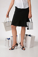 Single woman standing holding shopping bags