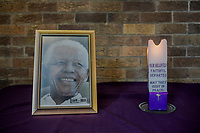 SOWETO, JOHANNESBURG, SOUTH AFRICA - DECEMBER 08: A photograph and a candle lay in remembrance to former President Nelson Mandela as parishioners (unseen) offer prayers during Sunday mass at the Regina Mundi Roman Catholic church in Soweto on December 8, 2013 in Johannesburg, South Africa. Mr Mandela, died on Thursday aged 95, spent 27 years in jail before becoming South Africa's first black president in 1994.<br /> Photo by Daniel Berehulak for The New York Times