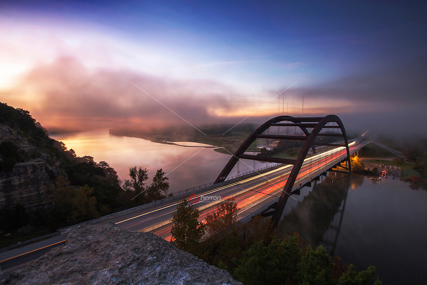 Fog rolls over the 360 Bridge during sunrise on a cold winter's morning on Lake Austin, Texas.
