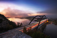 View from the 360 Overlook as fog rolls over the 360 Bridge during sunrise on a cold winter's December morning on Lake Austin, Texas.