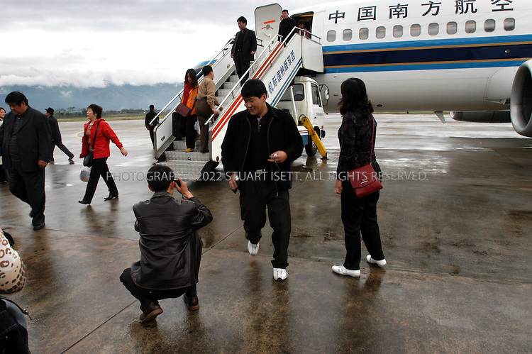 11/29/2004--Jinghong, China..Excited passengers disembark from a China Southern Airlines flight from Kunming to Jinghong in China's southern Yunnan province, and start to take photos to remember their trip. China's domestic air market is booming with thousands of first time flyers hitting the skies over China...Photograph by Stuart Isett.©2004 Stuart Isett. All rights reserved