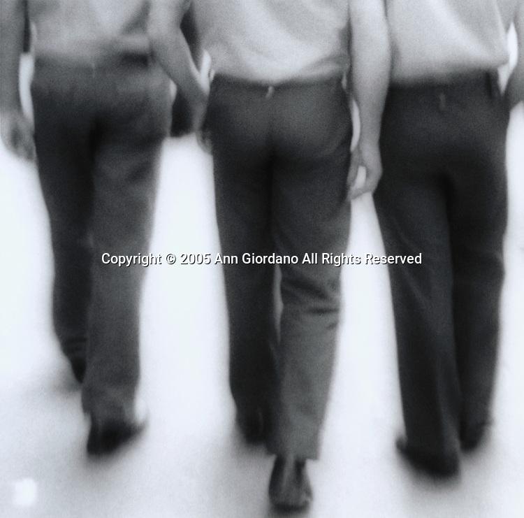Three Spanish men from behind walking down street