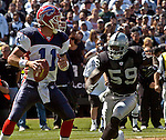 Oakland Raiders linebacker DeLawrence Grant (59) rushes Buffalo Bills quarterback Drew Bledsoe (11) on Sunday, September 19, 2004, in Oakland, California. The Raiders defeated the Bills 13-10.
