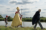The Bishop of Norwich Rev Graham James  arrives at St Benets Abbey. A Brother of St Benets leads the Bishop towards the ruined Abbey.