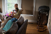 Fred Bermont and daughter Elyse Bermont (age 2.5) watch Sesame Street in their home in Lexington, Massachusetts, USA, before he goes to work and drops the kids off at day-care on June 9, 2014. Bermont is the father of two children and shares parenting duties with his wife, Jen Bermont. Fred usually takes care of the morning routine, including feeding, dressing, and dropping the kids off at day-care, and Jen picks them up and watches over them in the afternoon. Fred is a Senior Clinical Standards Specialist at Shire, a pharmaceutical company with headquarters in Lexington.