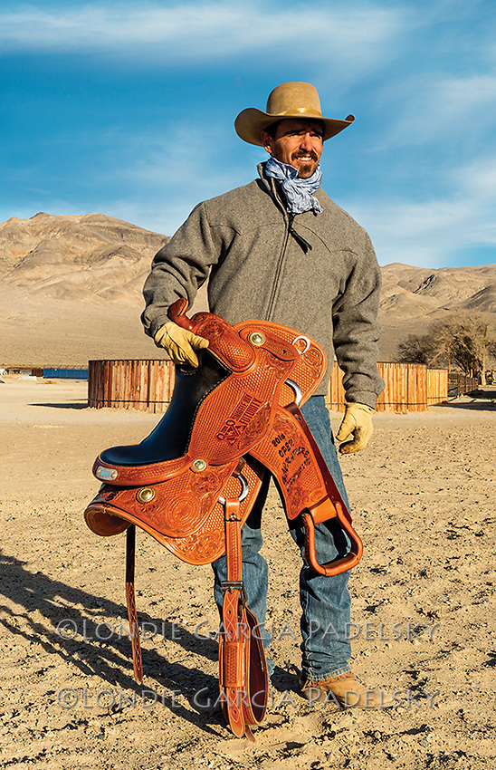 Nick Dowers holding one of his trophy saddles infront of his round corral at the Triple D Ranch. <br /> In 2014 Nick was the National Reined Cow Horse Association Snaffle Bit Futurity Open Champion.
