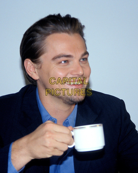 LEONARDO DICAPRIO.headshot, portrait, goatee, stubble, facial hair, smiling, drinking, coffee cup, mug.www.capitalpictures.com.sales@capitalpictures.com.© Capital Pictures.