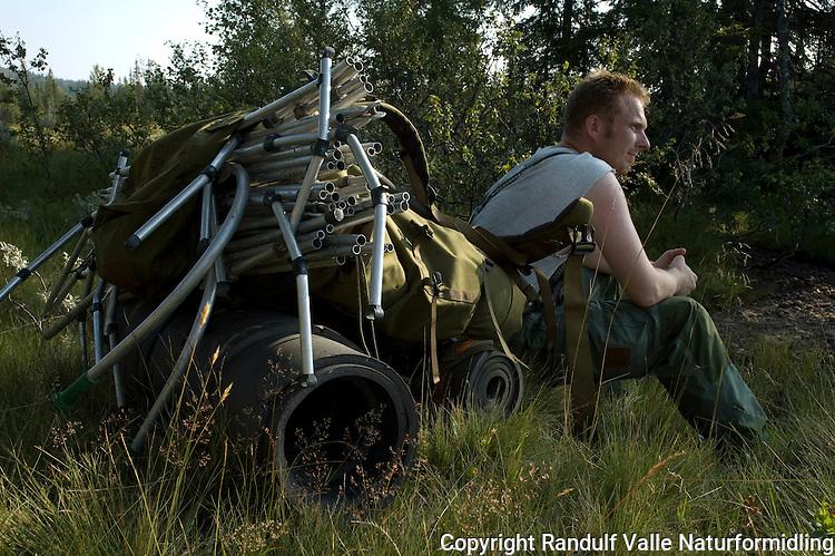 Mann med kano lastet på ryggsekk. ----- Man with canoe packed in backpack.