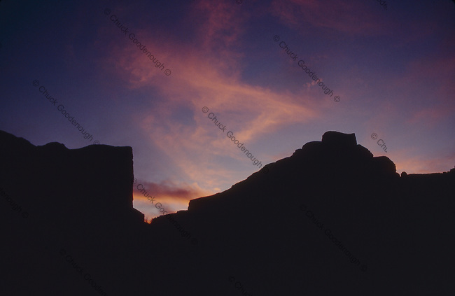 Stock photo of desert cliffs outlined in black silhouette by a purple sunset sky.