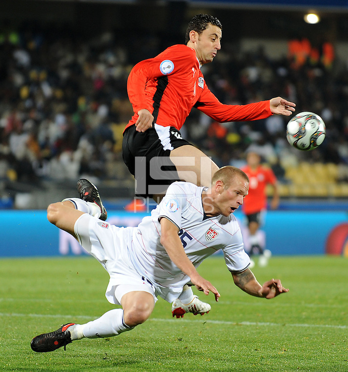 Jay DeMerit (below) of USA clears under pressure from Ahmed Farag (above) of Egypt. USA defeated Egypt 3-0 during the FIFA Confederations Cup at Royal Bafokeng Stadium in Rustenberg, South Africa on June 21, 2009..