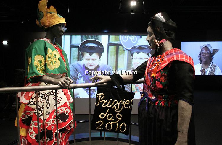 """Foto: VidiPhoto..ARNHEM - In het Nederlands Openluchtmuseum in Arnhem wordt maandag de laatste hand gelegd aan een voor Nederland unieke semi-permanente klederdrachtenexpositie. Vanaf donderdag zijn in het museum nog niet eerder getoonde Surinaamse kotomisi-kostuums te zien. Evenzo bijzonder is dat ze -als een soort Staphorstervariant- in combinatie met de Nederlandse streekdracht worden getoond. De expositie """"Kleding en identiteit"""" is in ieder geval te zien tot en met 2013 als wordt het herdacht dat het 150 jaar geleden is dat de slavernij werd afgeschaft."""