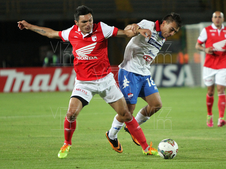 BOGOTA -COLOMBIA. 11-02-2014. Daniel Torres ( Izq) de Independiente Santa Fe de Colombia disputa el balon contra Derlis Orue Nacional  de Paraguay  durante el partido de ida de La Copa Bridgestone Libertadores de America   disputado en el estadio El Campin. / Daniel Torres (L)  of Independiente Santa Fe of Colombia fights for the ball against Nacional of Paraguay  Derlis Orue during firts  leg of the Copa Libertadores de America Bridgestone played at El Campin stadium . Photo: VizzorImage / Felipe Caicedo / Staff