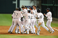 Lakeland Flying Tigers designated hitter Lance Durham (32) is mobbed by teammates including first baseman James Robbins (7), third baseman Tyler Hanover (9) after a walk off hit during a game against the Brevard County Manatees on April 10, 2014 at Joker Marchant Stadium in Lakeland, Florida.  Lakeland defeated Brevard County 6-5.  (Mike Janes/Four Seam Images)