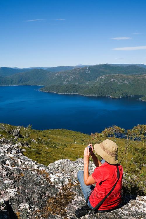 A woman photographs Lake Mackintosh from atop Mount Farrell, in Tasmania's western highlands.  Tullah, Tasmania, AUSTRALIA