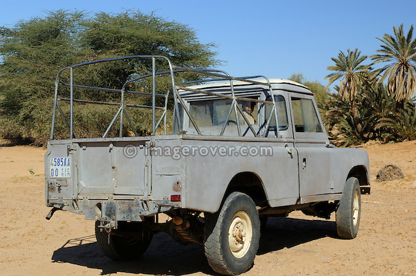 Africa, Mauritania, Sahara Desert, Ouadane. Little girl waiting inside an old Land Rover Series 3 long wheel base truck cab outside the old quarter of Ouadane. --- No releases available. Automotive trademarks are the property of the trademark holder, authorization may be needed for some uses.
