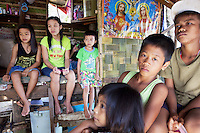 Philippines. Province Eastern Samar. Hernani. Barangay (neighbourhood) Carmel. Traditional hut. Rowina Calvadares (13 years old, wearing a green New York t-shirt) with her sister Rica (left, 11 years) and brother Ric (right, 7 years) are seated on the floor of their one room house. Two other brothers and a small sister ​​are also in the house. The boy and girls are orphans. A religious catholic poster with Jesus and the Virgin Mary is on the wall. The roof and the walls of their house were damaged by typhoon Haiyan's winds. Typhoon Haiyan, known as Typhoon Yolanda in the Philippines, was an exceptionally powerful tropical cyclone that devastated the Philippines. Haiyan is also the strongest storm recorded at landfall in terms of wind speed. Typhoon Haiyan's casualties and destructions occured during a powerful storm surge, an offshore rise of water associated with a low pressure weather system. Storm surges are caused primarily by high winds pushing on the ocean's surface. The wind causes the water to pile up higher than the ordinary sea level. 25.11.13 © 2013 Didier Ruef