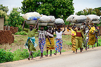 BURKINA FASO, Provinz Poni, Gaoua, women from villages carry charcoal for income generation to the market in town / Frauen aus Doerfern tragen Produkte wie Feuerholz und Holzkohle zum Markt in der Stadt