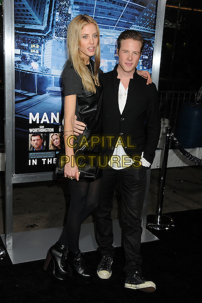 guest & Ashton Holmes.L.A. Premiere of  'Man on a Ledge' held at The Grauman's Chinese Theatre in Hollywood, California, USA..January 23rd, 2012 .full length black dress tights jacket jeans denim clutch bag.CAP/ADM/BP.©Byron Purvis/AdMedia/Capital Pictures.