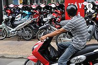 Man on motor scooter watching bike store (Licence this image exclusively with Getty: http://www.gettyimages.com/detail/83154227 )
