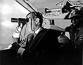 Aboard the USS Hornet - (FILE) -- United States President Richad M. Nixon follows Apollo 11 recovery activities with binoculars aboard the USS Hornet, located 13 miles (20.9215 km) from the spacecraft's splashdown point.  The President led the nation in greeting astronauts Neil A. Armstrong, Michael Collins, and Edwin E. Aldrin, Jr., at the successful completion of their historic lunar landing mission on July 24, 1969.  Their spacecraft splashed down 900 miles (1448.41 km) southwest of Hawaii at 12:50 p.m. EDT July 24, 1969 eight days after the space pilots were launched by a Saturn V space vehicle from the Kennedy Space Center..Credit: NASA via CNP