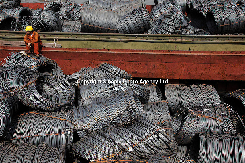 Workers rest on a barge full of steel wires docked at a steel stockyard run by the Shanghai Yirong Trading Company Ltd in Shanghai, China..10 Apr 2009