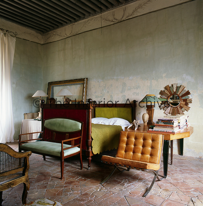 A traditional bedroom with an interesting mix of furniture styles, such as an antique wooden bed, which contrasts with a classic Mies van der Rohe Barcelona chair. The room has a rustic feel with a beamed ceiling and tiled floor. The stone walls are painted with natural pigments inspired by the colours of Provence, while being careful to leave the original underlying layers.