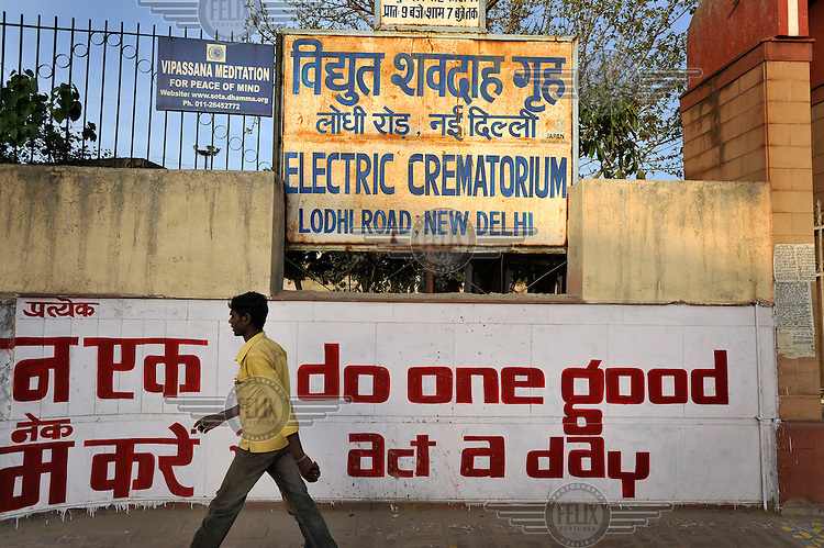 A sing in English and Hindi reading 'do one good act a day', underneath a sign for a crematorium.