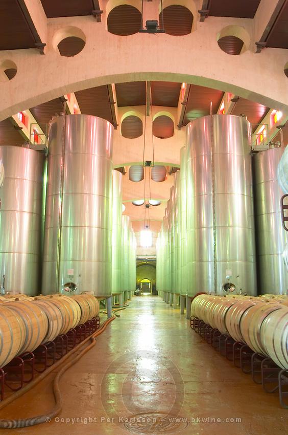 Wine aging in oak barrels. Modernista style vaulted winery. Oak barrel aging and fermentation cellar. Fermentation tanks. Raimat Costers del Segre Catalonia Spain