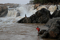 A fisherman, helped by his son, tightens his fishnet between two rocks, Khone falls, Laos-2010