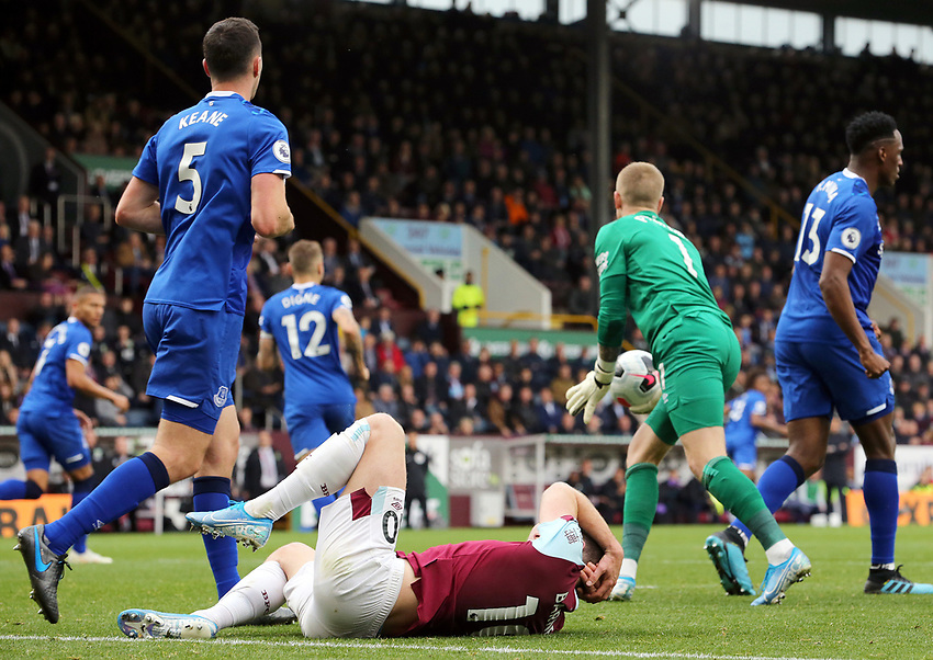 Burnley's Ashley Barnes lies grounded holding his head following a collision with Everton's goalkeeper Jordan Pickford who in the meantime sets himself to re-distribute the ball<br /> <br /> Photographer Rich Linley/CameraSport<br /> <br /> The Premier League - Burnley v Everton - Saturday 5th October 2019 - Turf Moor - Burnley<br /> <br /> World Copyright © 2019 CameraSport. All rights reserved. 43 Linden Ave. Countesthorpe. Leicester. England. LE8 5PG - Tel: +44 (0) 116 277 4147 - admin@camerasport.com - www.camerasport.com