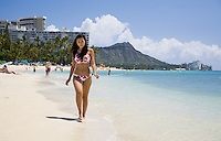 Attractive woman in heart pattern bikini walking down Waikiki Beach with Diamond Head in background