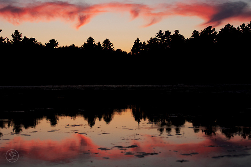 Sunset clouds and pine trees reflect on Balsam Lake, Killarney Provincial Park, Ontario, Canada